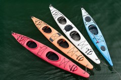 four colorful fiberglass kayaks